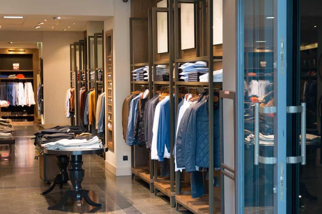 Bekleidungsgeschäft mit geöffneter Tür und verschiedenfarbigen Hemden im Innenraum