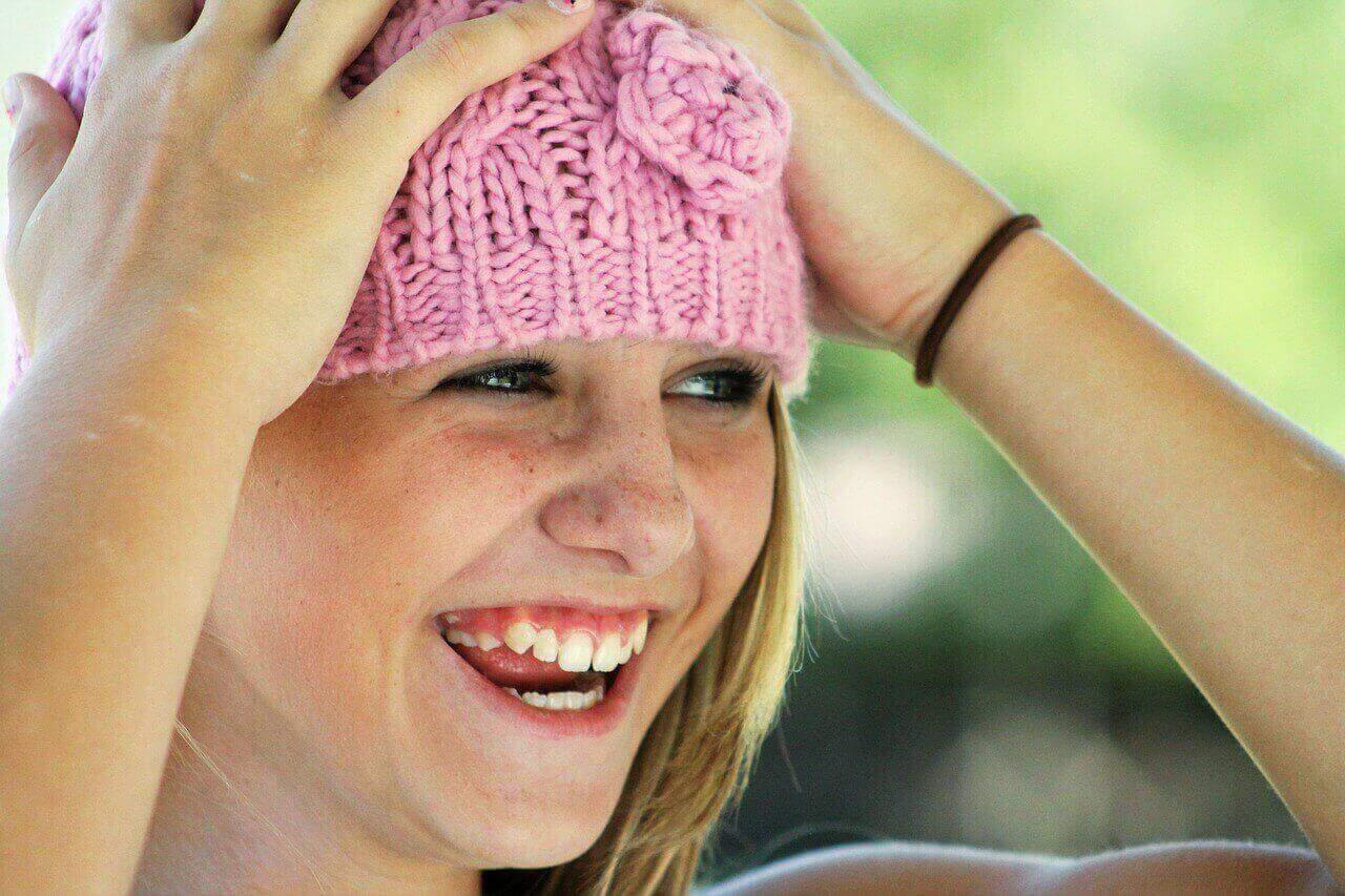 Lachendes Mädchen mit rosa Mütze hält sich den Kopf