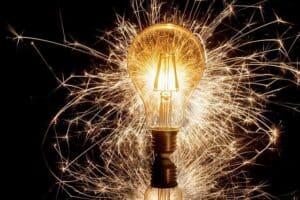 Leuchtende Glühbirne mit sprühenden Funken um sich herum