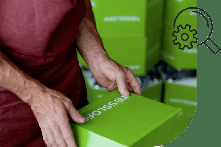 Mitarbeiter beklebt grünen Holzwürfel mit weißem Tessloff-Logo