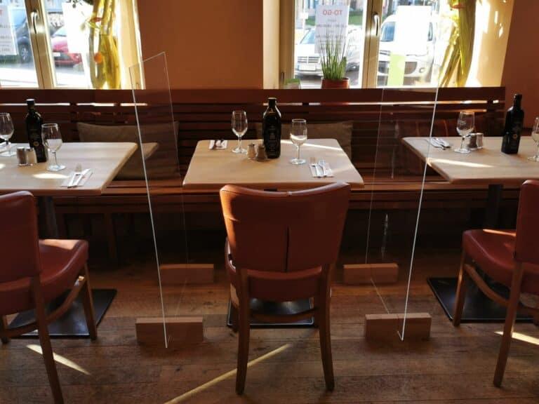 Hygiene-Trennwand zwischen Tischen und Stühlen im Restaurant