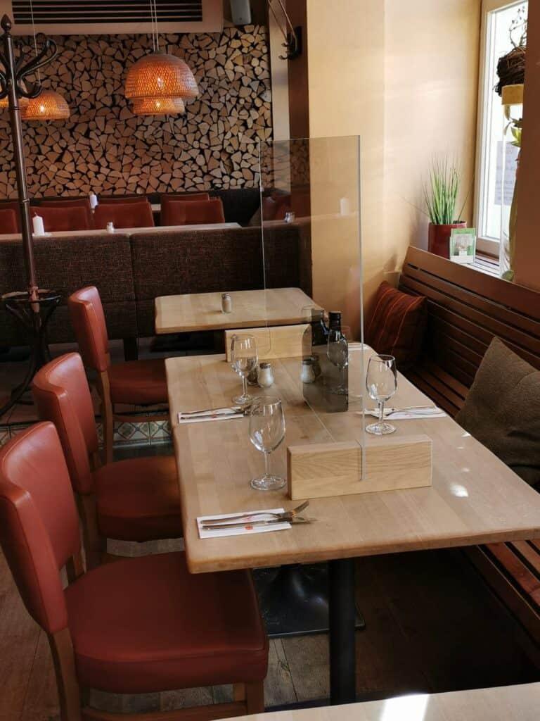 Hygiene-Trennwand auf Tisch als Infektionsschutz im Restaurant