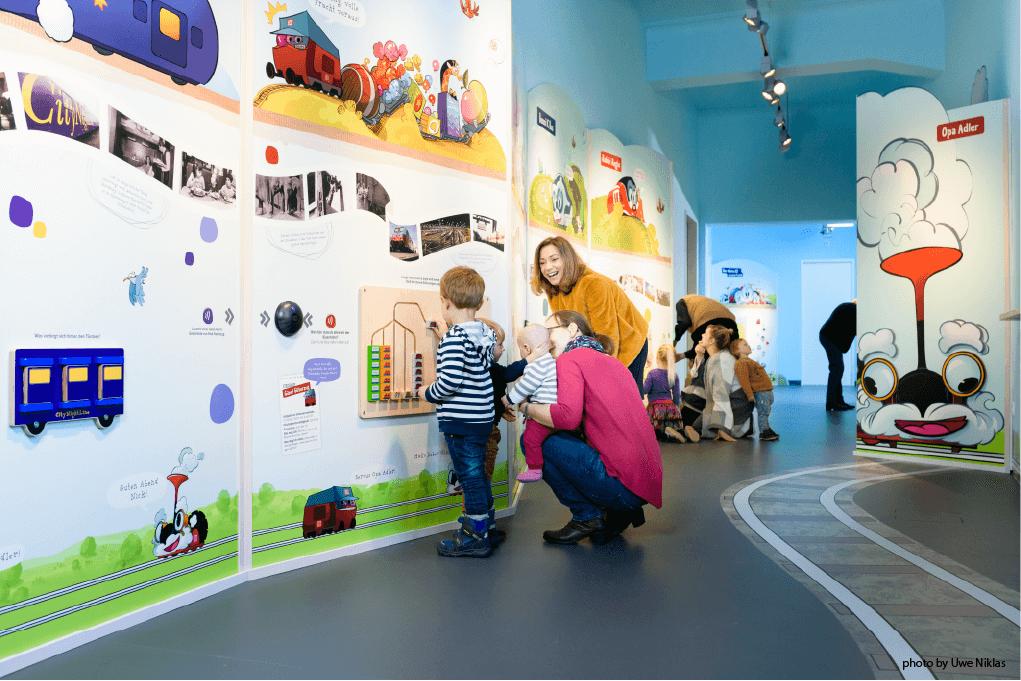 Ladenbau Wandelemente und spielende Familie im Kindermuseum