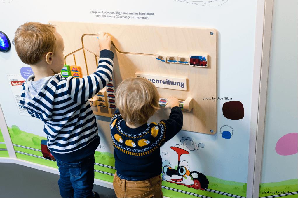 Ladenbau Wand mit Spielelementen und zwei kleinen spielenden Kindern