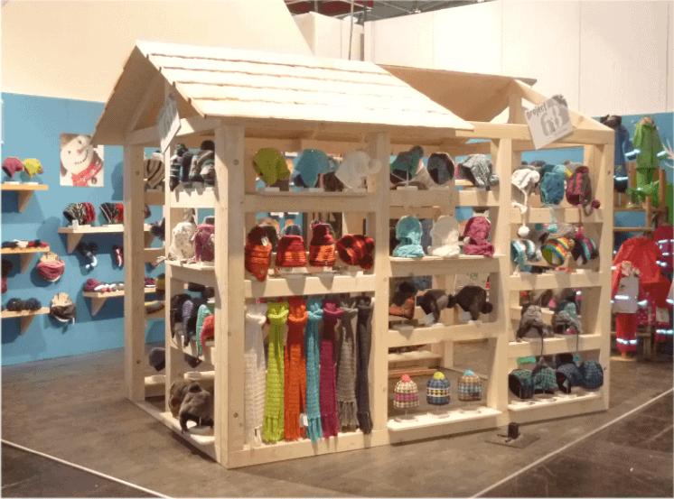 Kleines Holzhaus mit Mützen und Schals bestückt als Ladenbauelement auf Messestand