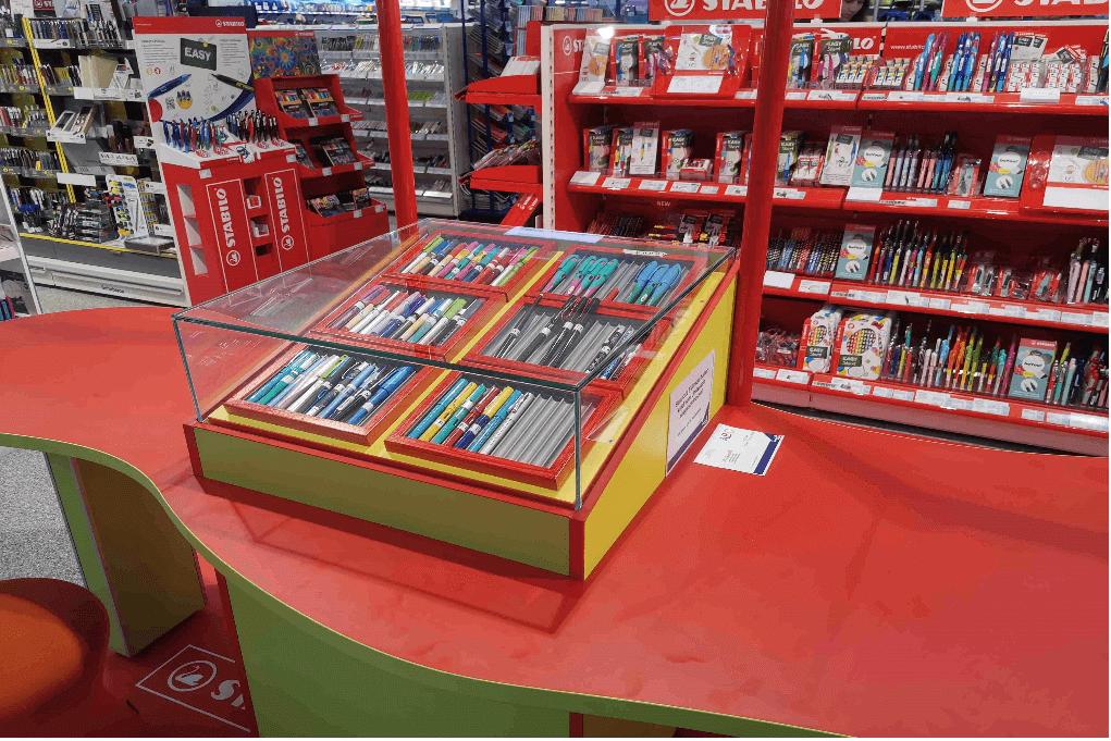 Shop-in-Shop-Lösung Tisch mit roter Arbeitsfläche und Auslage für Füller