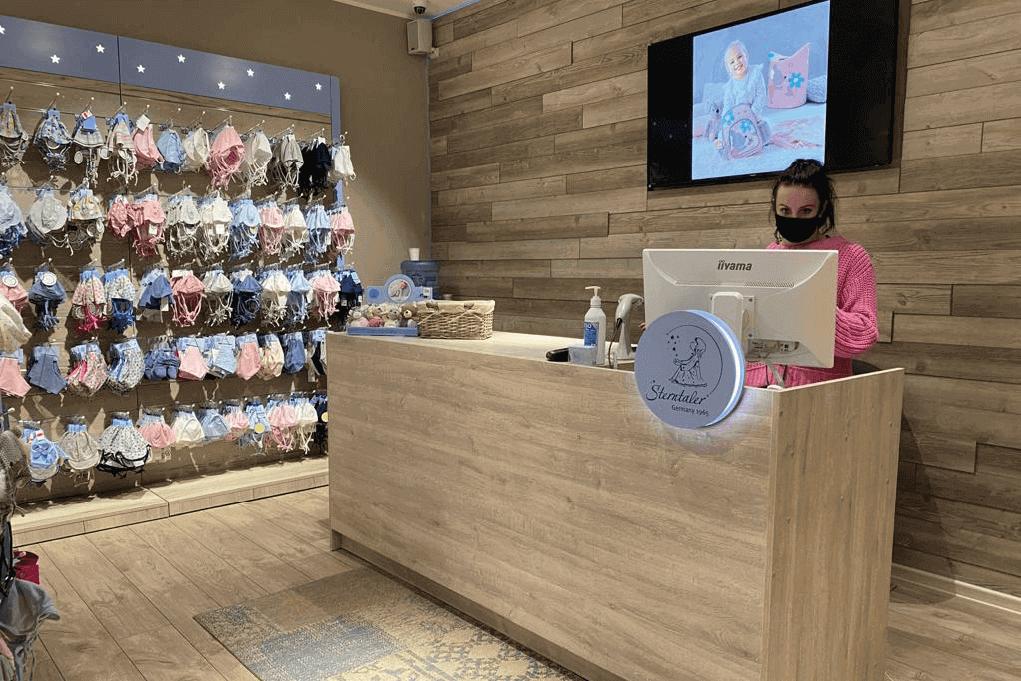 Ladenbau im Ladengeschäft von Sterntaler mit Kassenbereich aus Holz und Logo-Emblem