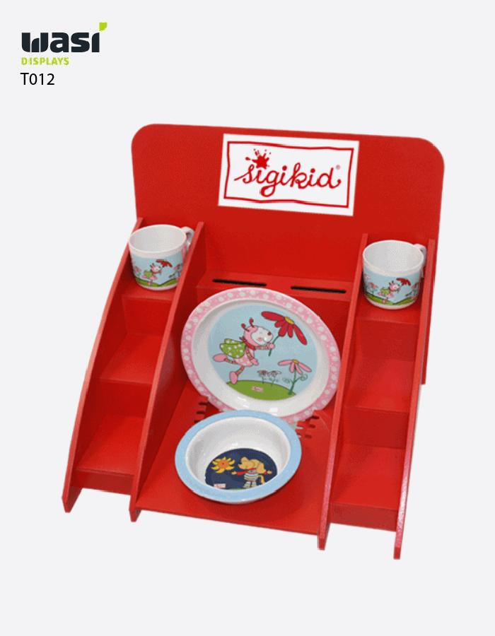 Abgestuftes und rot lackiertesThekendisplay Modell T012 mit Sigikid-Logodruck und mit Kindergeschirr bestückt