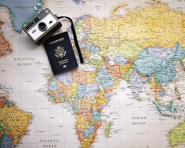 Alter Fotoapparat und amerikanischer Reisepass auf bunter Weltkarte liegend